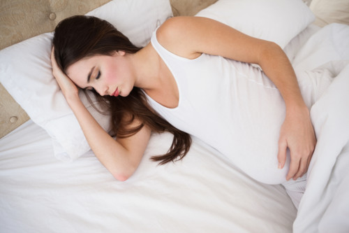 Pregnant brunette sleeping in bed at home in the bedroom